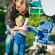 Young Woman Mother Wears Jacket On Son Little Boy On Walk In Spring. Outdoor Portrait