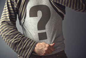 Questioning concept. Casual man showing question mark printed on his shirt.